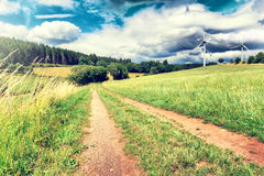 Summer landscape with country road and wind turbines Stock Images