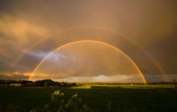 Summer landscape with a double rainbow Stock Images