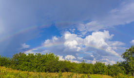 Summer landscape with double rainbow, green grass and clouds Royalty Free Stock Image