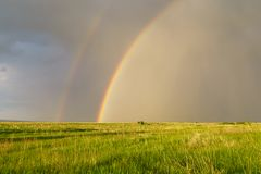 Summer landscape with a double rainbow over a field in a thunder. Storm Royalty Free Stock Photography