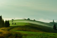Summer landscape with foggy hills and green grass. Royalty Free Stock Images