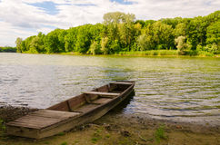 Chained wooden boat at the lake. The place is one of the backwaters of the Tisza river in Tiszadob, Hungary. Royalty Free Stock Image
