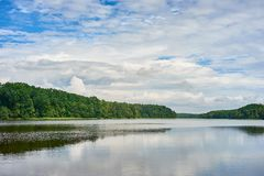 Summer landscape with forest lake under a blue cloudy sky Stock Images