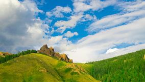 Summer landscape high hill with large stones and blue sky with air clouds. Russia Siberia. stock photos