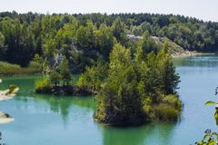 Summer landscape in Kostopil granite quarry, Ukraine. Lake in Kostopil granite quarry, Rivne Oblast, Ukraine. Summer landscape with blue lake Stock Photos