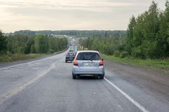 Cars drive along the highway past a green forest in the evening. Summer landscape.  Krasnoyarsk Territory, Russia. Cars drive along the highway past a green Royalty Free Stock Photos