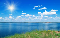 Summer landscape with lake. Summer landscape with quiet water of lake, blue cloudy sky and green grass Royalty Free Stock Photo