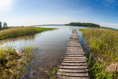Summer landscape with lake and wooden bridge Stock Images