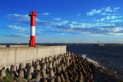 The lighthouse on the pier and breakwaters. Summer landscape with lighthouse on the pier and breakwaters Stock Photography