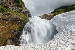 Summer landscape - mountain waterfall falling into the snowfield Stock Image