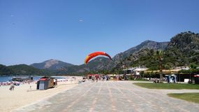 Summer landscape with mountains, sea, beach, umbrella, palm trees and paragliding falling on the seaside boulevard. The cover of the site stock photography