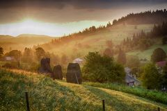 Summer landscape in mountains with traditional hay stacks on hillside. Typical rural scenery of Carpathians Stock Photo