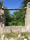 Summer landscape. Old abandoned village on the empty field. Destroyed abandoned house standing in the forest Stock Images