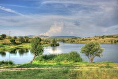 Summer landscape in Bulgarian countryside. Summer landscape with a picturesque lake and fluffy clouds somewhere in Bulgarian countryside Stock Images