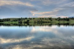 Summer landscape in Bulgarian countryside. Summer landscape with a picturesque lake and fluffy clouds somewhere in Bulgarian countryside Royalty Free Stock Photos