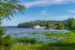 Summer landscape with pier and small harbour in northern village. Ladoga lake bay in sunny day. Beautiful rural scenery, travel. Blog concept. Lahdenpohja stock image