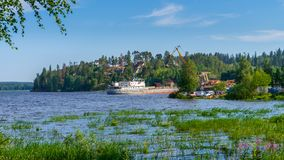 Summer landscape with pier and small harbour in northern village. Ladoga lake bay in sunny day. Beautiful rural scenery, travel. Blog concept. Lahdenpohja royalty free stock image