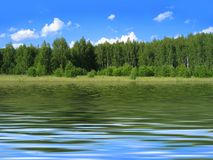 Summer landscape reflected in water. Summer landscape with bright blue sky and trees reflected in water Stock Photography