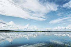 Summer landscape with reflection of cumulus clouds on water Royalty Free Stock Image