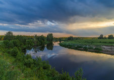 Summer landscape, river flows between green banks. On the horizon of the forest, dark blue clouds Stock Image