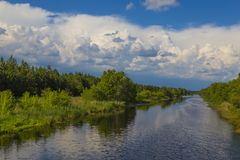 Summer landscape: river in the forest. Summer landscape: quiet narrow river surrounded by green forest against the blue cloudy sky. Ukraine, forest-steppe royalty free stock image