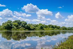 summer landscape: a river in which white curly clouds are displayed_ stock image