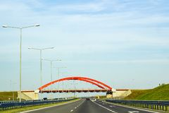 Summer landscape with road, cars and red arch of bridge. Cars driving on asphalt road. Summer landscape with road, red arch of bridge over track and metal street Stock Photo