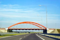 Summer landscape with road, cars and red arch of bridge. Cars driving on asphalt road. Summer landscape with road, red arch of bridge over track and metal street Royalty Free Stock Images
