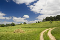 Summer landscape with road, a meadow and hay Stock Images