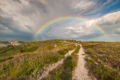 Summer landscape with road and rainbow. Majestic sky after thunderstorm Stock Photo