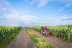 Summer landscape road, wheat field, motocycle. And blue clouds Stock Image