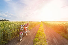 Summer landscape road, wheat field, motocycle. And blue clouds Stock Photo