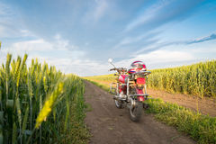 Summer landscape road, wheat field, motocycle. And blue clouds Stock Photography