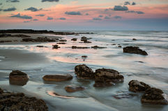 Summer landscape with rocks on beach during late evening and low Stock Photos