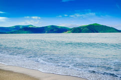 Summer landscape, the sand on the beach, blue sea with waves. Gr Stock Photography