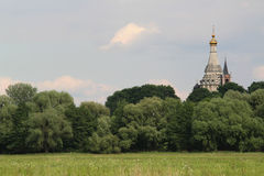 Summer landscape. Whis trees and steepled church Stock Photos