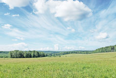 Summer landscape with wide meadow and beautiful clouds Stock Images