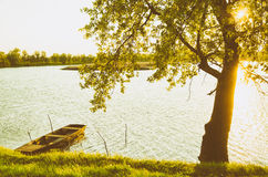 Summer landscape - wooden boat, backwater, tree and sunset Stock Photo