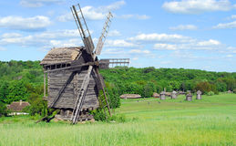 Summer landscape with wooden mills and cloudy sky Royalty Free Stock Image