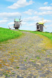 Summer landscape with wooden mills and cloudy sky Stock Photos