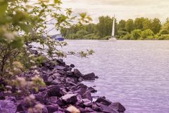 Yacht and ship on background of lake, opposite shore. Summer lake, beach with stones, Summer landscape. Seasons, ecology. Summer landscape with Yacht and ship on Stock Photo