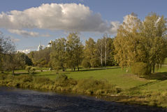 Summer lanscape. Green park in Pskov city with river, clouds and distance church Royalty Free Stock Photo