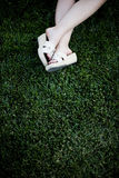 Summer leisure. Woman sitting on the grass in summer leisure with her legs and shoes showing on the lawn outside Stock Photos