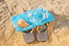 Summer leisure activity kit concept. Top view of blue shoes flip flop, diving mask, shell and towel on sandy background. Summer leisure activity kit concept Royalty Free Stock Photography