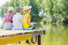 Summer leisure. Rear view of three children sitting at bank and fishing Royalty Free Stock Images