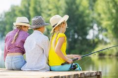 Summer leisure. Rear view of three children sitting at bank and fishing Royalty Free Stock Photo