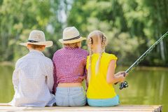 Summer leisure. Rear view of three children sitting at bank and fishing Stock Images
