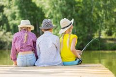 Summer leisure. Rear view of three children sitting at bank and fishing Royalty Free Stock Image