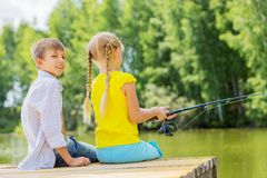 Summer leisure. Rear view of two children sitting at bank and fishing Royalty Free Stock Photo