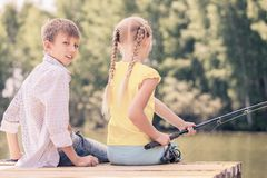 Summer leisure. Rear view of two children sitting at bank and fishing Royalty Free Stock Image